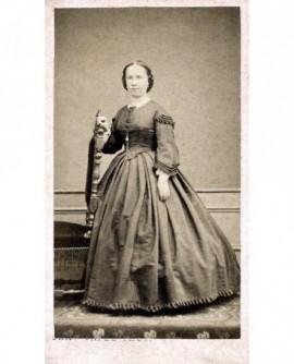 Jeune femme debout en robe, appuyée sur une chaise