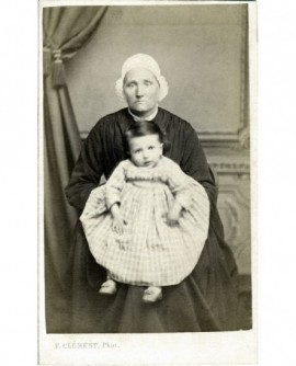 Nourrice en coiffe portant un bébé dans ses bras.