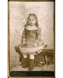 Petite fille en robe ourlée de dentelle assise