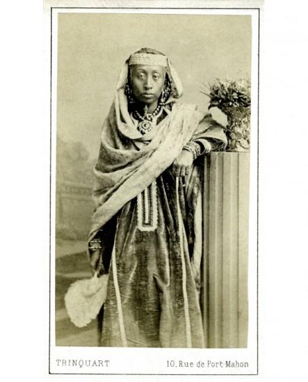 Femme noire drapée debout, chasse-mouche à la main