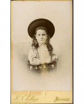 Petite fille au grand chapeau, appuyée sur une chaise