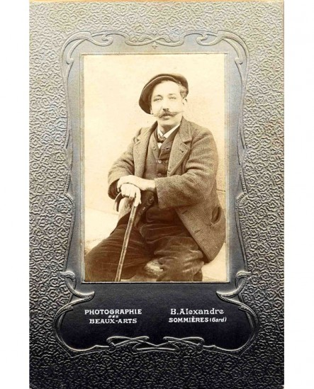 Homme moustachu en casquette tenant une canne
