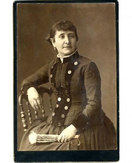 Femme posant assise, un éventail à la main