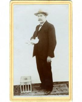 Homme (collombophile) posant debout une collombe à la main