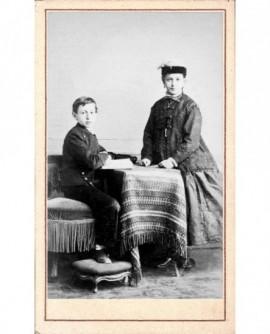 Jeune fille en turban et garçon en uniforme de collégien assis à une table