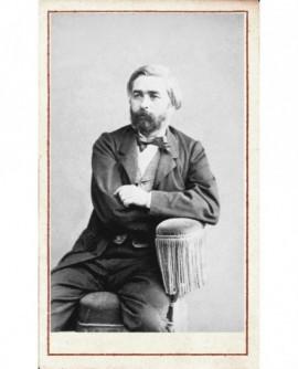 Homme barbu assis bras croisés