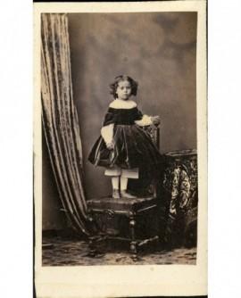 Petite fille en robe noire, debout sur une chaise