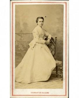 Jeune fille en robe blanche, debout accoudée à une chaise