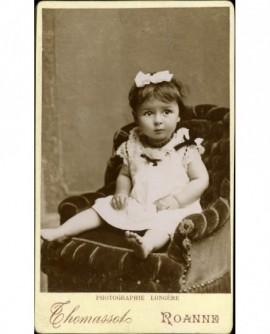 Petite fille en chemise, pieds nus, assise sur un fauteuil
