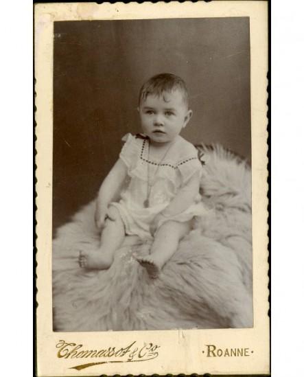 Bébé en chemise, pieds nus, assis sur une peau de mouton