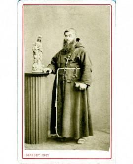 Capucin barbu debout, près d'une statue de la Vierge