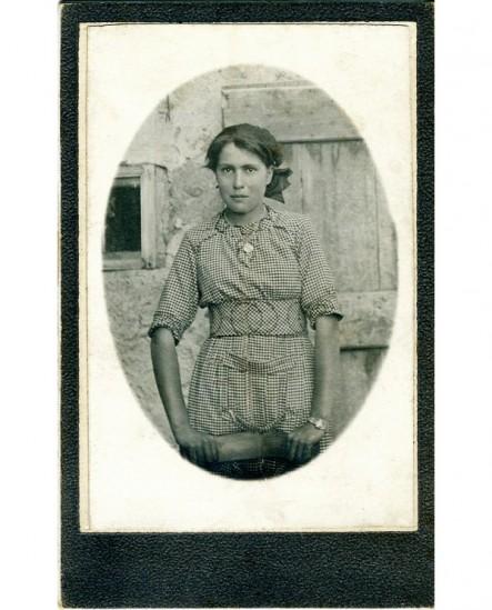 Jeune paysanne en robe appuyée sur une chaise, devant sa ferme