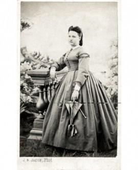 Jeune fiemme en robe debout, accoudée à une balustrade, une ombrelle à la main