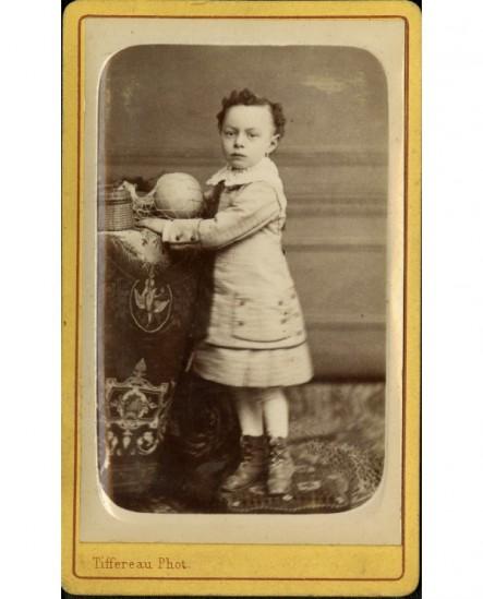 Petite fille debout, appuyée sur une table avec ballon