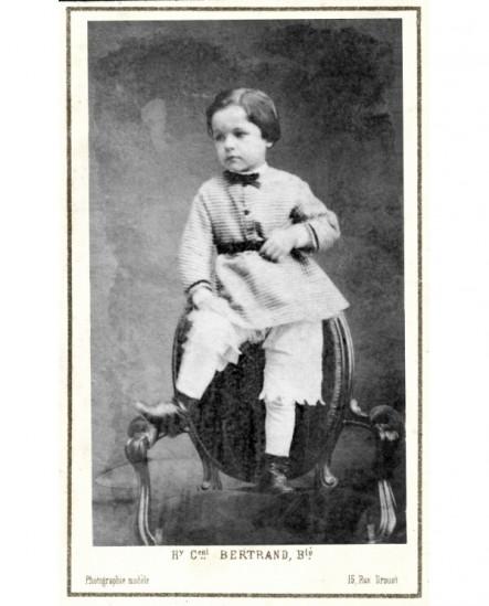 Petit garçon debout sur un fauteuil, un pied sur un bras