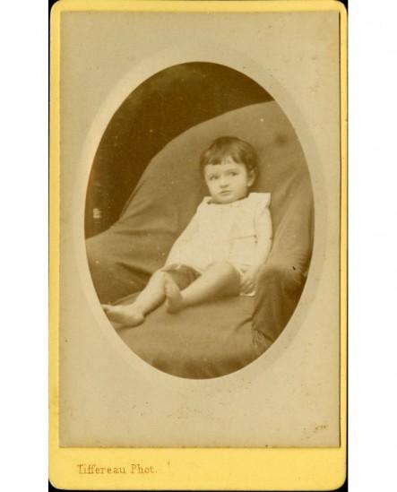 Jeune enfant en chemise, assis sur un fauteuil
