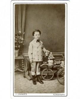 Garçon en costume à coté d'un cheval à roulette .