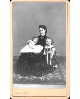 Jeune femme en robe à volants assise, avec 2 enfants (l'un sur ses genoux)