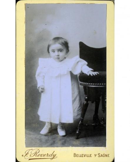 Enfant en robe se tenant à une chaise