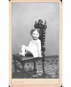 Fillette en chemise assise sur une chaise en bois tourné