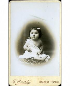Bébé en chemise épaule dénudée assis sur un coussin