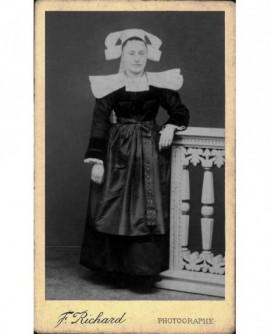 Femme en costume breton appuyée sur une balustrade