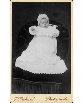 Bébé en robe blanche et crémeau de baptême. Marguerite Petit