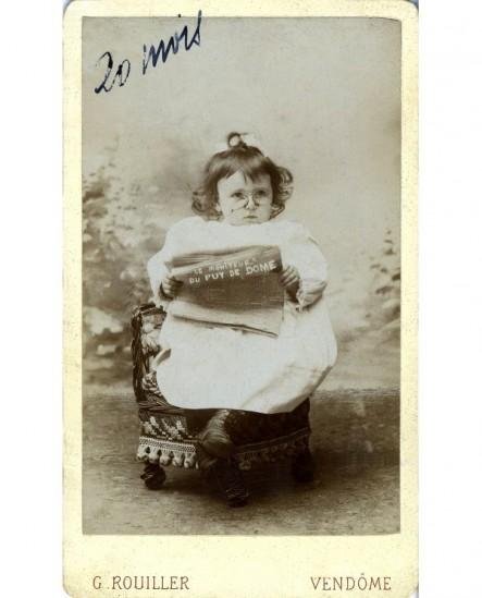 """Fillette assise lisant le journal \""""Le moniteur du puy de Dôme\"""""""""""""""