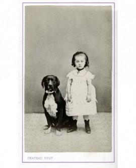 Fillette debout avec un chien assis à ses côtés