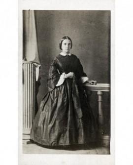 Femme debout appuyée sur une table