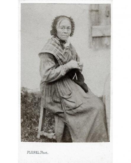 Femme agée en bonnet et en tablier assise tricotant
