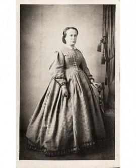 Femme en robe à carreaux debout, appuyée sur une chaise
