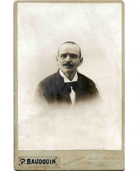 portrait d'un homme à cheveux ras et moustache en pointe
