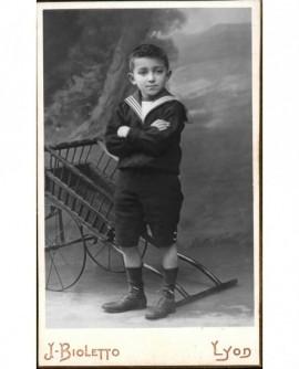 Garçon en costume marin devant charrette à bras