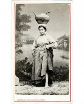 Femme portant un pot en terre sur la tête