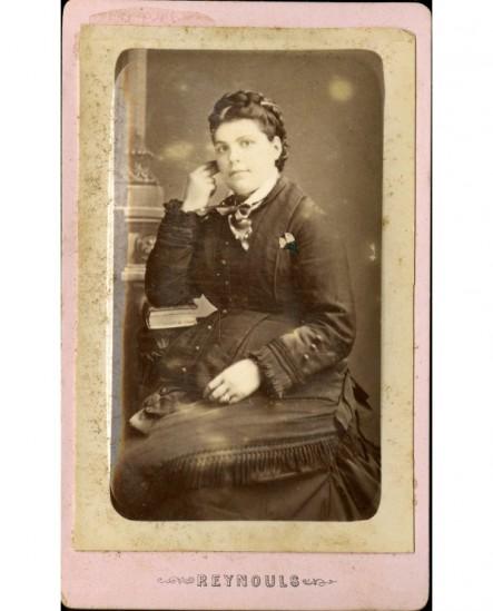 jeune femme assise un livre sous le coude