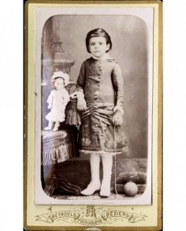 Petite fille debout avec poupée et balle