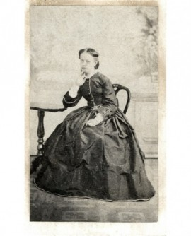 Femme en robe assise, accoudée à un guéridon, se tenant la tête