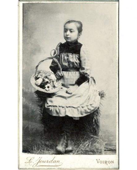 Fillette assise sur une botte de paille, un panier de fleurs à la main