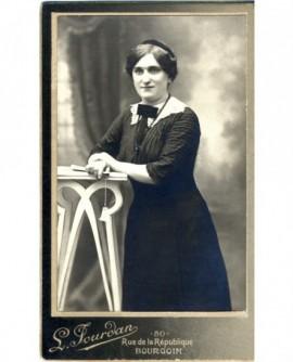 Femme en robe appuyée sur une sellette, éventail