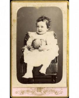 Jeune enfant en robe assis avec balle