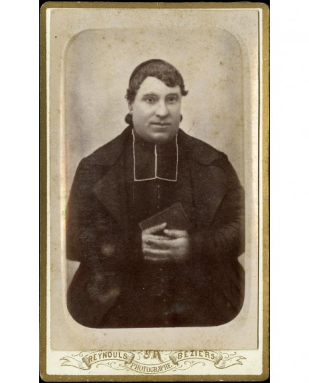 Ecclésiastique en calotte assis, mains sur bréviaire