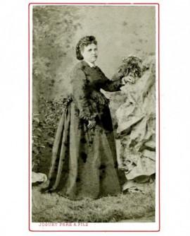 Femme en robe debout, appuyé sur un massif