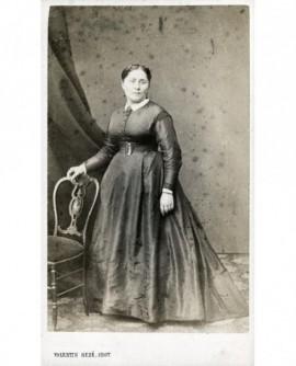 Femme en robe accoudée à une chaise