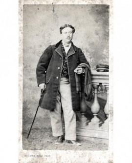 Homme appuyé sur une balustrade, canne et cigare à la main