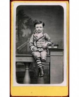 Garçon en culotte courte assis sur une rembarde