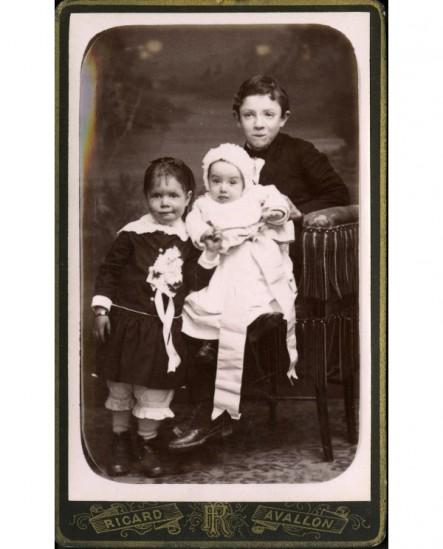 Trois jeunes enfants, bébé sur les genoux de l'aîné