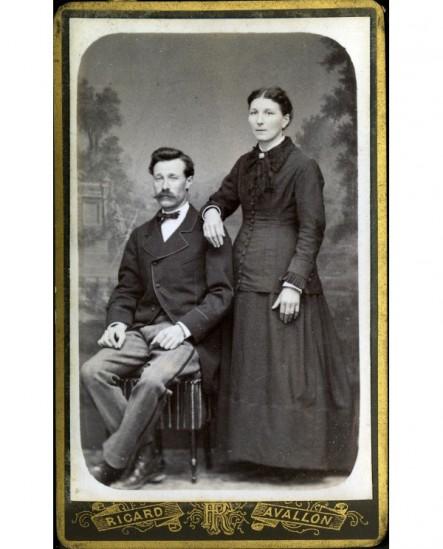 Homme à moustache assis et femme debout