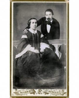 Couple: femme assise, homme debout derrière