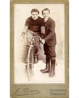 Cycliste sur son vélo, tenu par un autre homme